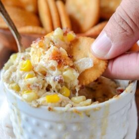 Hot Crab, Corn and Bacon Dip in a white baking dish with someone dipping a cracker