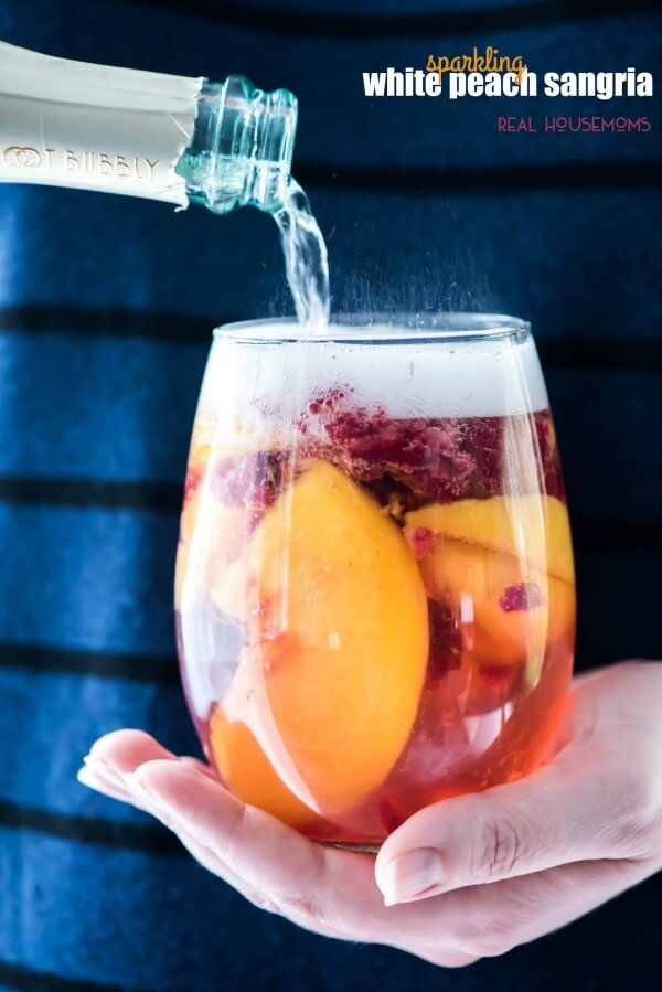 A Glass of Sparkling White Peach Sangria with Peach Slices Inside