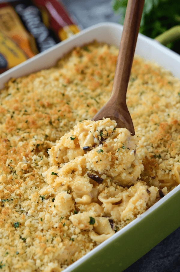 Scooping out a Spoonful of Cauliflower Mac Cheese from a Green Serving Dish