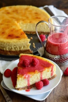 A Slice of Creme Brulee Cheesecake Beside the Remaining Cheesecake on a Wooden Table