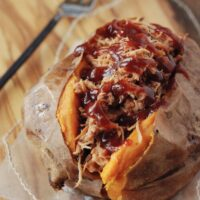 A Pulled Pork Stuffed Sweet Potato on a Piece of Parchment Paper
