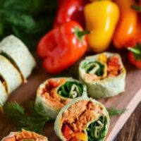 Pinwheels on wood board stuffed with sweet and spicy salmon, spinach, bell peppers, dill and cream cheese
