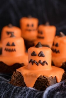 Six Melted Jack O' Lantern Brownies on a Black Surface Covered in Fake Spider Webs