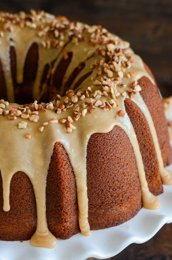 Sweet Potato Cream Cheese Bundt Cake with Praline Frosting! Looking for an impressive cake you can serve for dessert or breakfast? This rich, moist, sweet potato spiced cake is swirled with sweet cream cheese and topped with a pecan praline frosting.