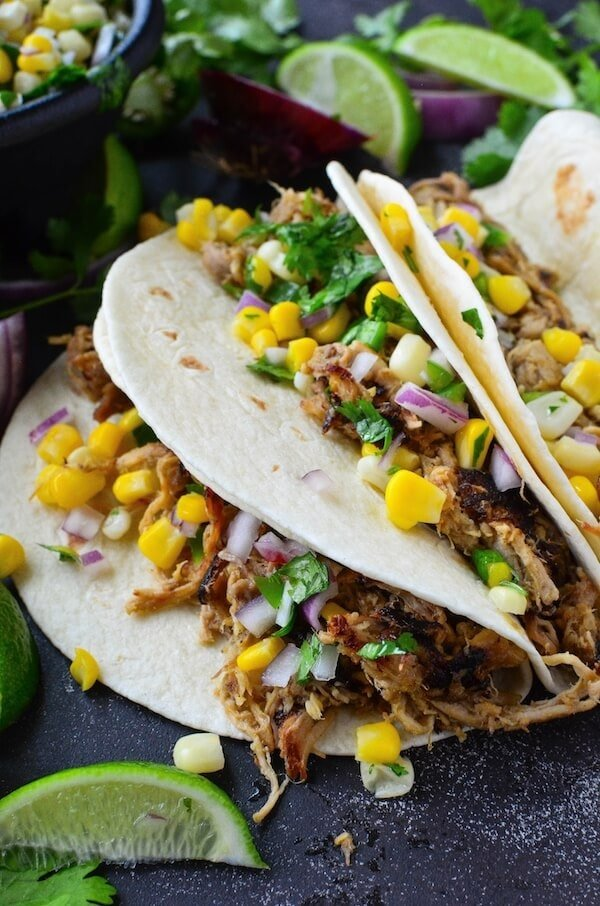 Crispy Pork Carnitas with Corn Salsa - easy pork carnitas are made in a slow cooker or instant pot and then pan fried till crispy. Serve them as tacos with fresh corn salsa, with rice and beans or with eggs for breakfast!