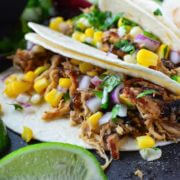 Crispy Pork Carnitas with Corn Salsa - easy pork carnitas are made in a slow cooker or instant pot and then pan fried till crispy. Serve as tacos with fresh corn salsa, with rice and beans or with eggs for breakfast!