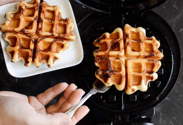 Cinnamon Roll Waffles being taken out of a waffle iron and placed on a plate.
