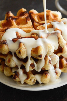 A stack of cinnamon roll waffles drizzled with maple cream cheese syrup.