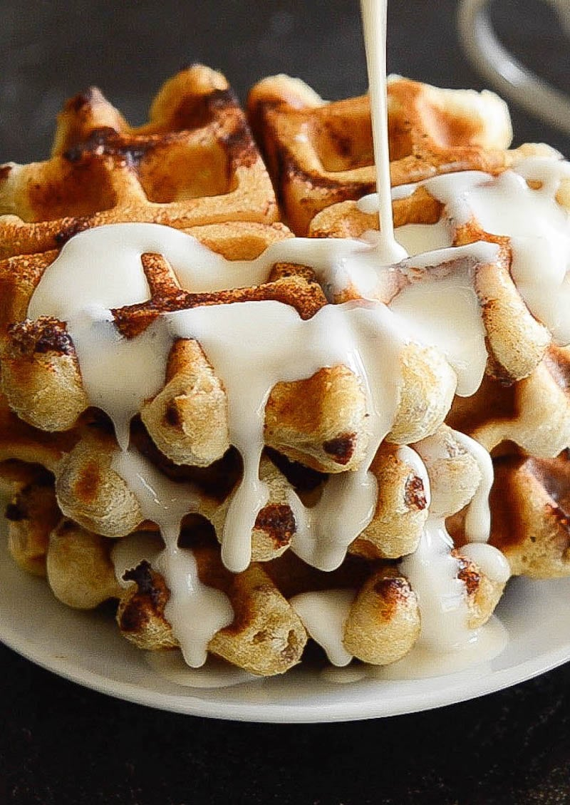 A Stack of Cinnamon Roll Waffles being Drizzled with Maple Cream Cheese Syrup