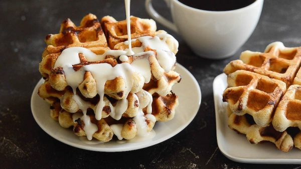 Cinnamon Roll Waffles on a plate being drizzled with cream cheese sauce.