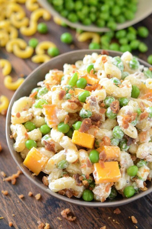Bacon Ranch Pasta Salad in a bowl with bacon, cheese and peas.