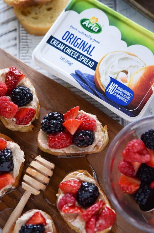 Berries & Cream Crostini! Buttery crostini toast with sweetened cinnamon cream cheese, fresh berries and honey!