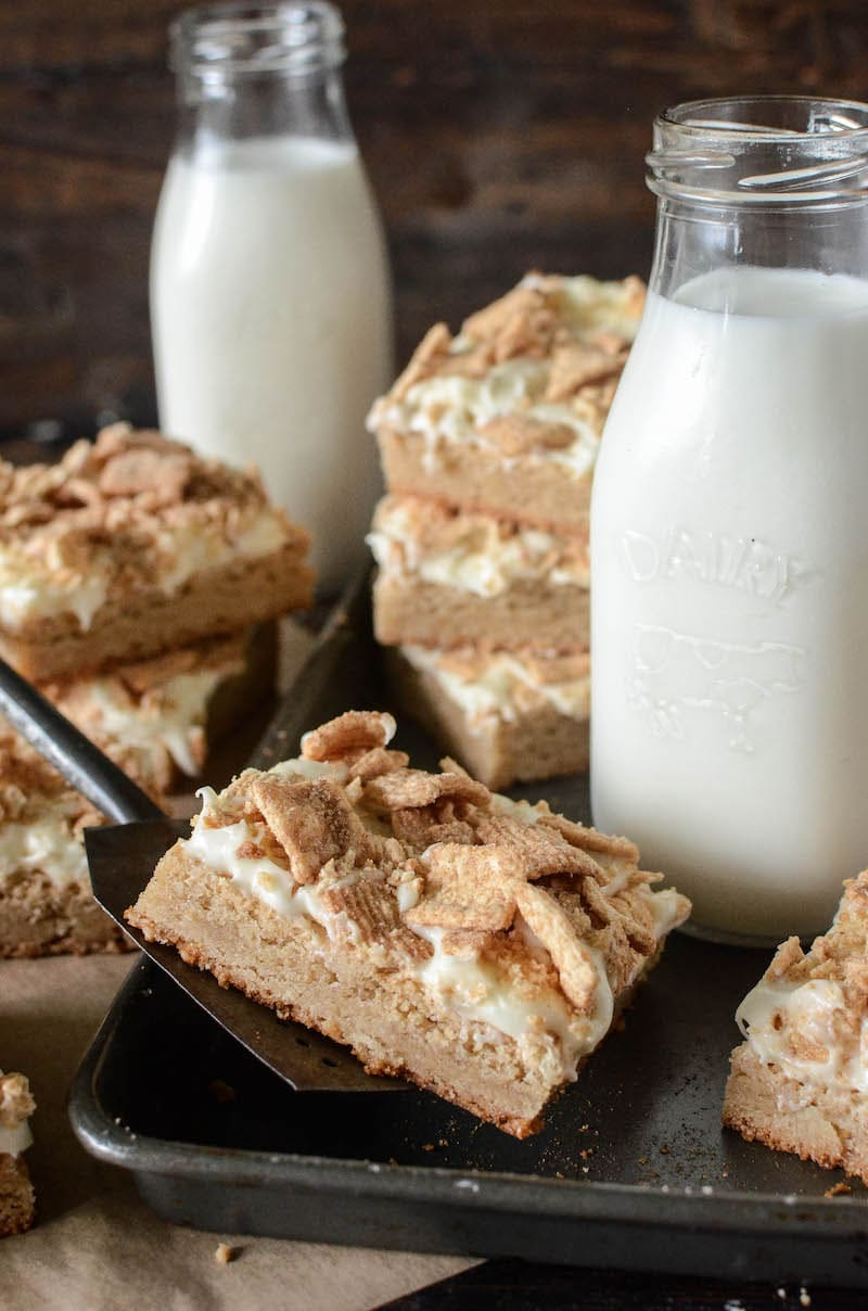 A Pan Filled with Cinnamon Toast Crunch Bars and a Tall Glass of Milk with More Bars and Milk in the Background