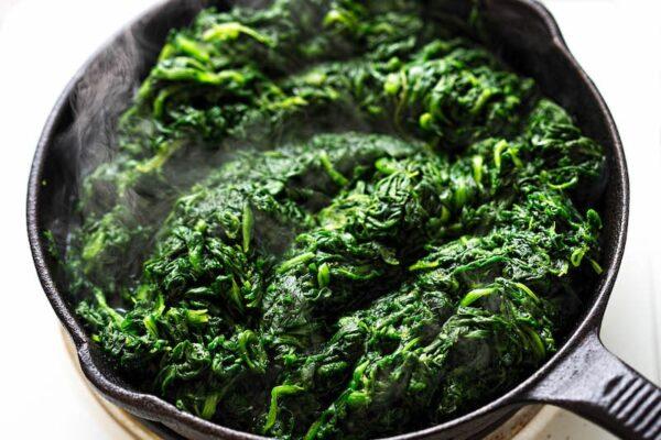 Frozen spinach in a skillet being thawed.