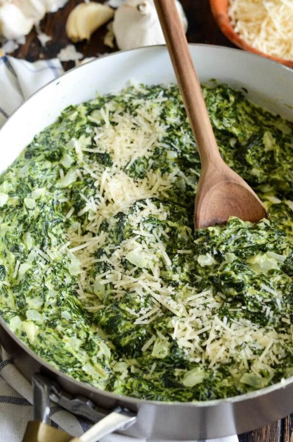 Creamed spinach with parmesan cheese on top in a skillet.