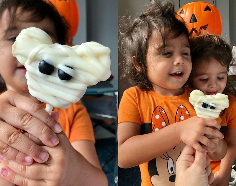Two Photos of Ellie Holding a Mickey Mouse Mummy Pop