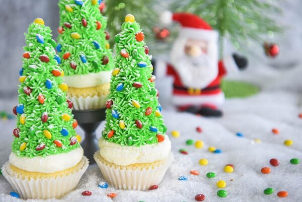 Christmas Tree Cupcakes: these festive Christmas decorated cupcakes are made with buttercream frosting, mini m&ms and hidden ice cream cones for the base!