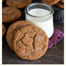 Up close image of ginger doodle cookies with a glass of milk and a napkin.