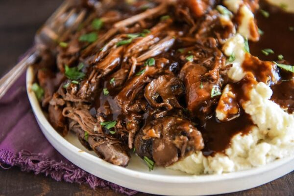 Slow Cooker Beef Pot Roast: a favorite family recipe for an extra flavorful tender beef pot roast that is always an instant favorite! You will never guess the secret ingredients! #SlowCooker #CrockPot #PotRoast