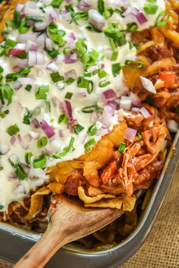 Pulled Pork Corn Chip Pie: upgrade your favorite tailgate food with this easy pulled pork chili corn chip pie served with cheddar cheese, sour cream and onions!