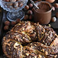 Nutella Crescent Ring surrounded by eggs, hazelnuts, and nutella