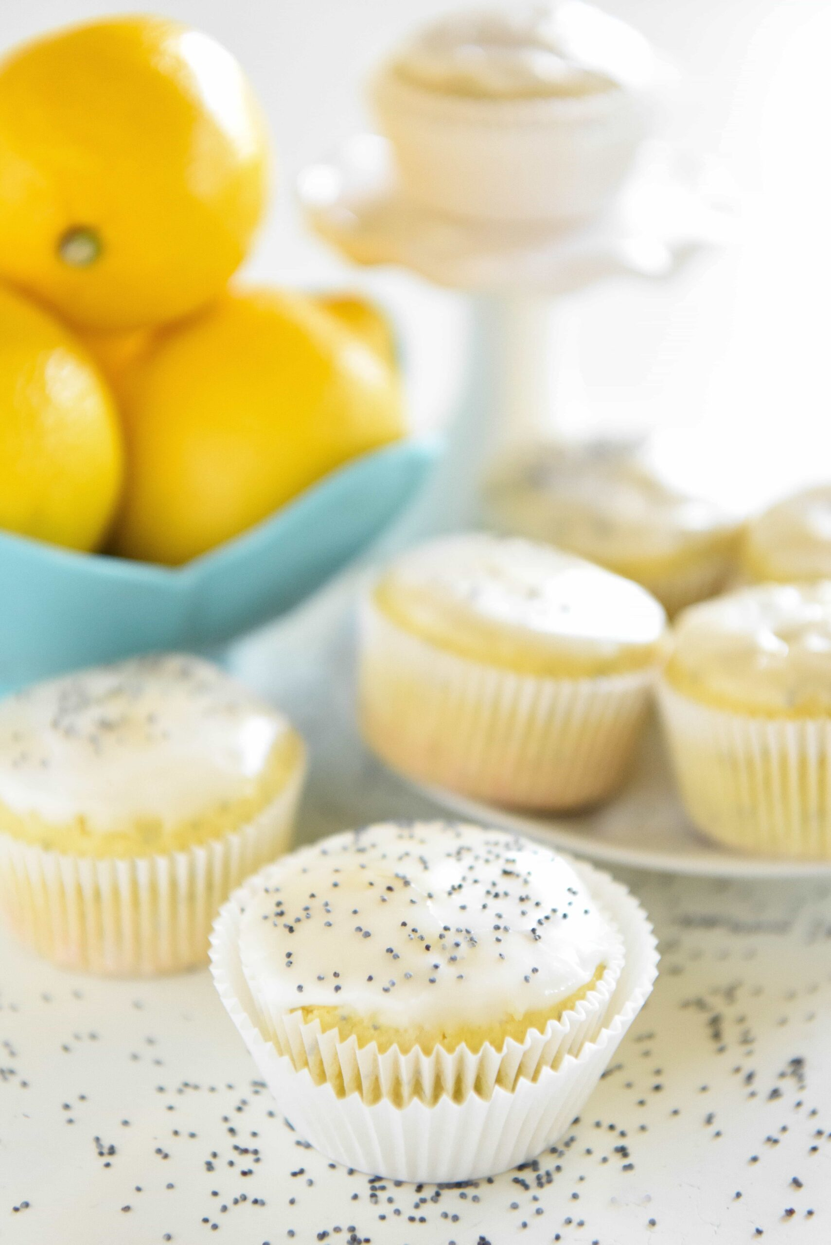 A Single Lemon Poppy Seed Muffin on a Poppyseed-Covered Countertop with More Muffins in the Background