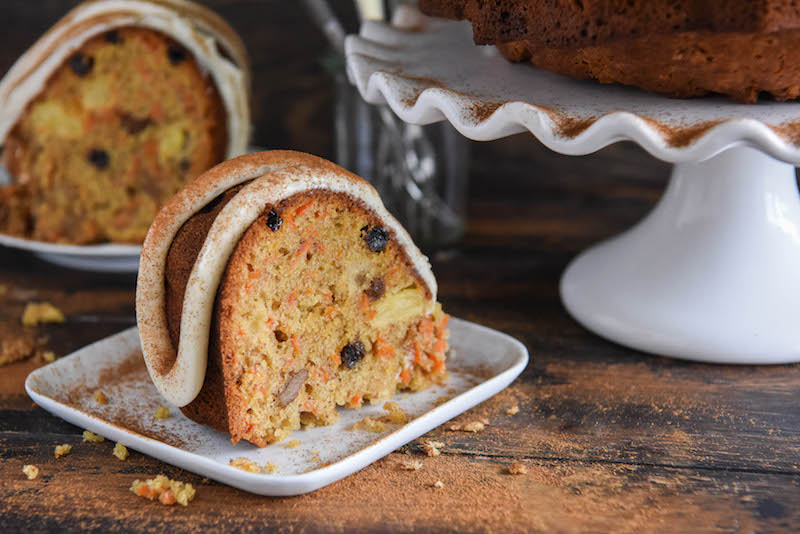 A Piece of Carrot Bundt Cake Beside Another Slice and the Rest of the Cake on a Cake Stand