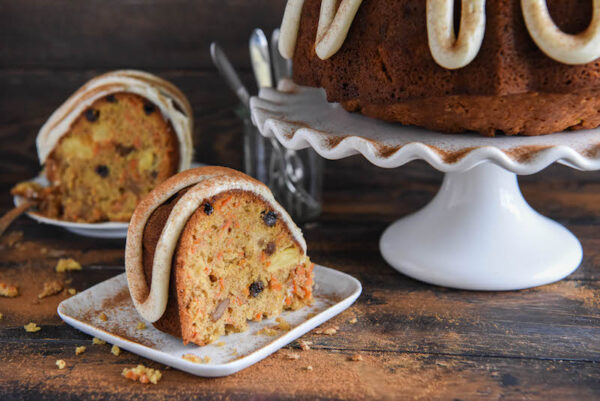 Loaded Carrot Bundt Cake: a moist carrot cake, made with a pound of carrots, is loaded with pineapple, nuts, raisins and topped with whipped cream cheese frosting!