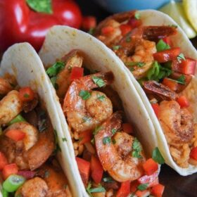 Three shrimp tacos on a platter with a bell pepper in back ground