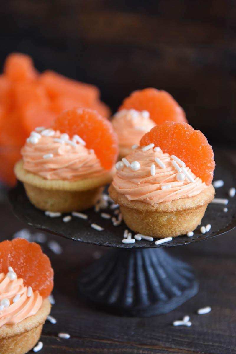Orange Creamsicle Cookie Cups: soft sugar cookie cups are filled with orange creamsicle icing and topped with orange candy wedges. #orange #cookie