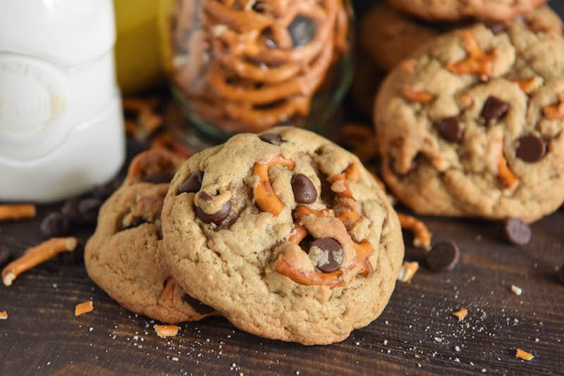 Three Chunky Monkey Cookies on a Table with a Jar of Pretzels