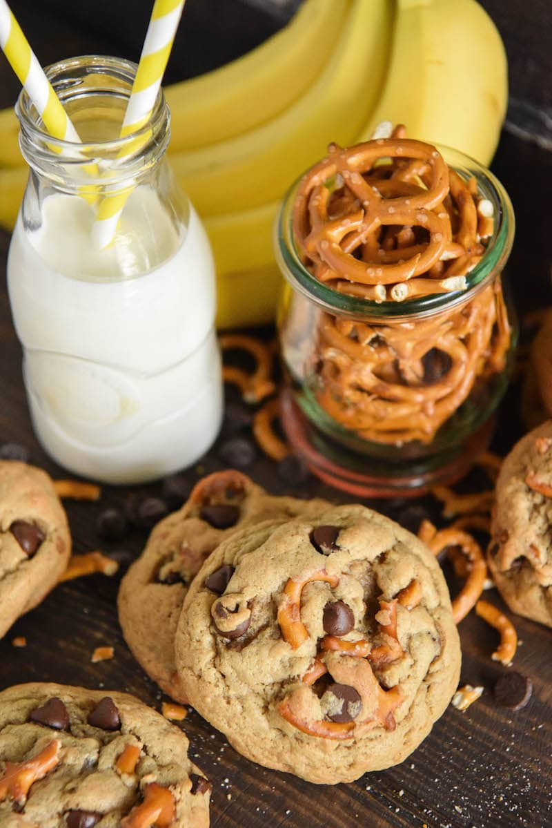 Five Chunky Monkey Cookies Beside a Glass of Milk, a Bunch of Bananas and a Jar of Pretzels