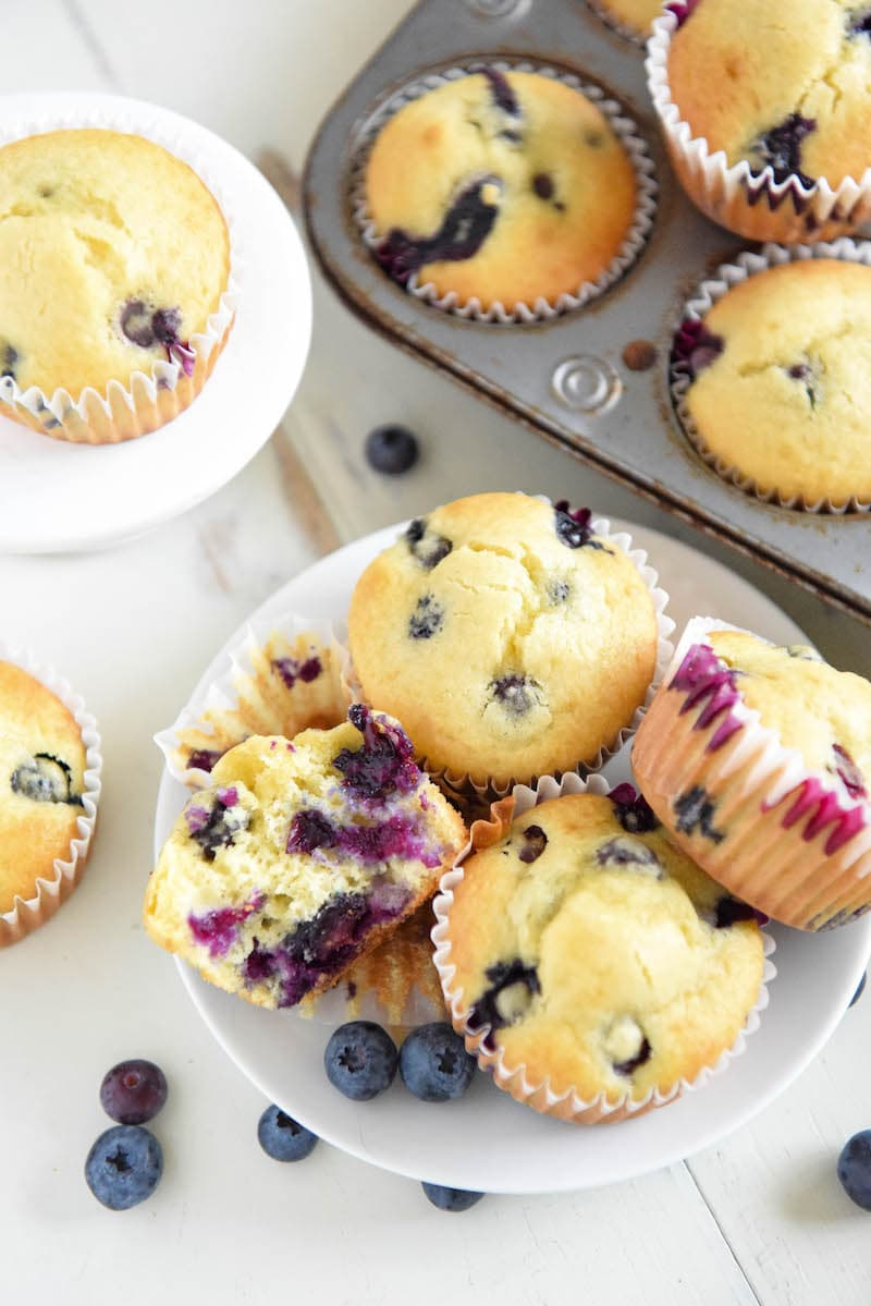 A Plate Full of Blueberry Muffins with More Muffins in a Pan Beside the Plate