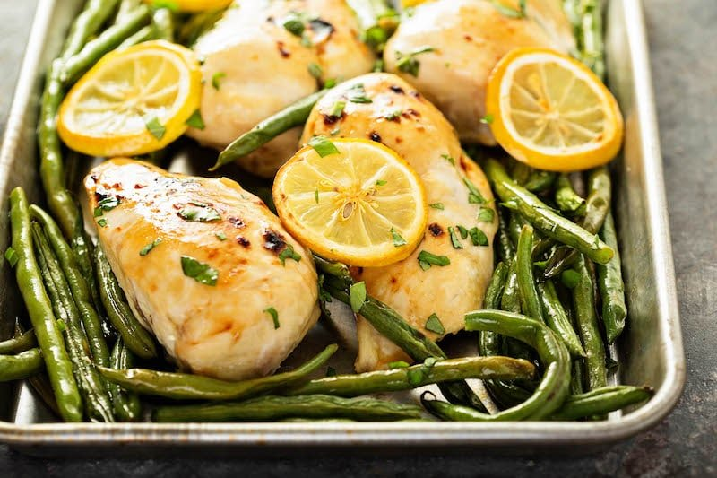 Roasted chicken breast with lemon and green beans on sheet pan.