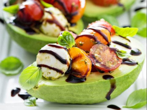 Caprese Stuffed Avocado: a refreshing caprese salad is tossed with a bright green pesto, piled into avocados and topped with fresh basil and a balsamic glaze. #salad #lowcarb #avocado #caprese