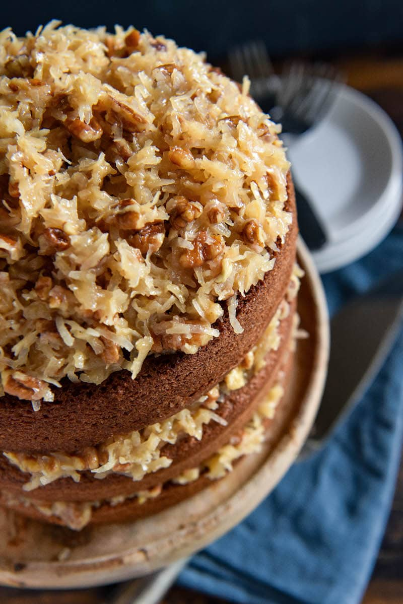 A German Chocolate Layer Cake on Top of a Light Brown Cake Stand