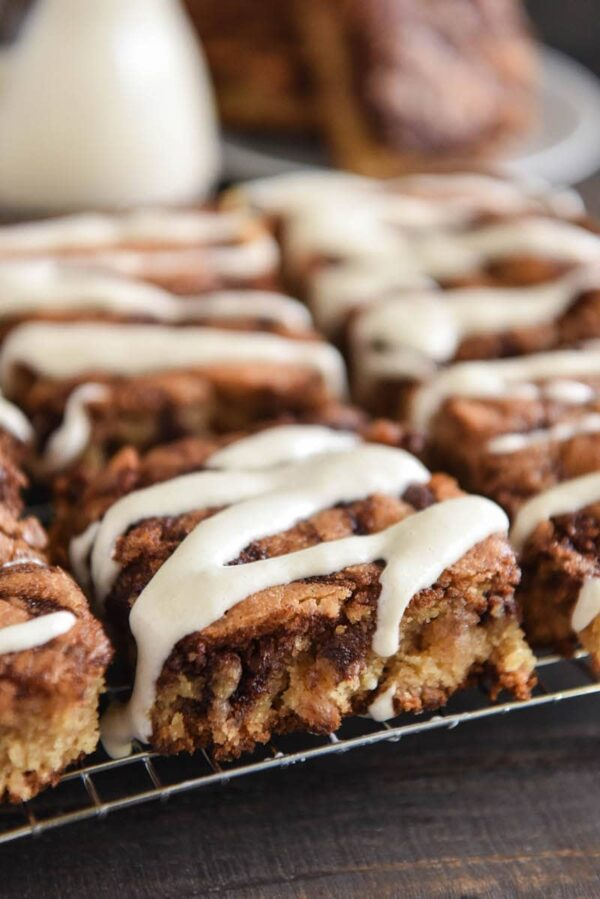 Cinnamon Roll Blondies: super soft blondies are swirled with a sweet cinnamon brown sugar filling and served warm with a drizzle of cream cheese icing! #Blondies #Dessert #CinnamonRoll