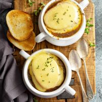 This Crockpot French Onion Soup recipe is loaded with flavor from slow cooking all day with a rich, silky broth and classic broiled cheesy toast topping! #FrenchOnionSoup #Soup #Crockpot #SlowCooker