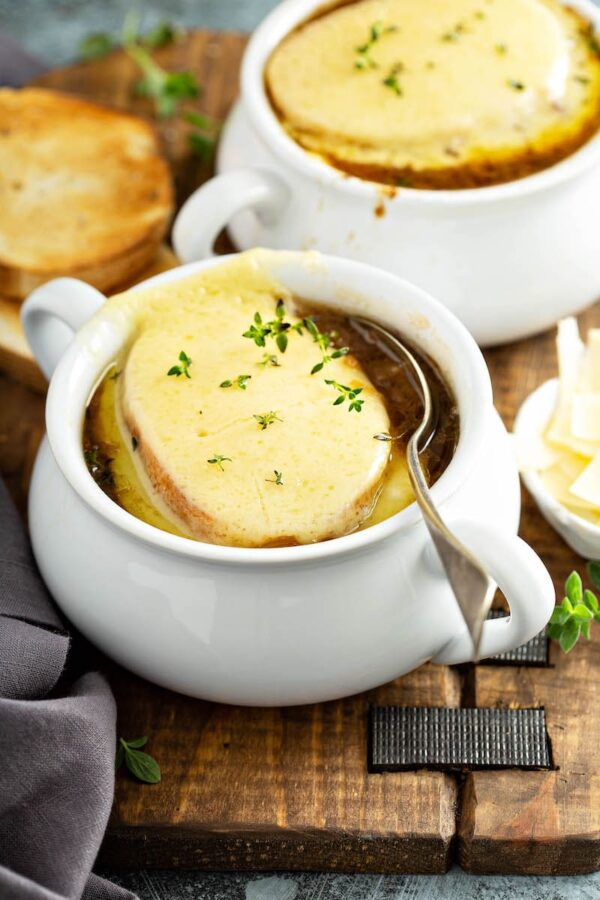 French Onion Soup made in the crockpot served in big bowls with a spoon inside ready to take a bite.