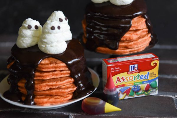 Halloween Ghost Pancakes: a big stack of homemade orange pancakes are topped with dark chocolate ganache and whipped cream ghosts for a spooky Halloween treat! #Halloween #Breakfast #Pancakes