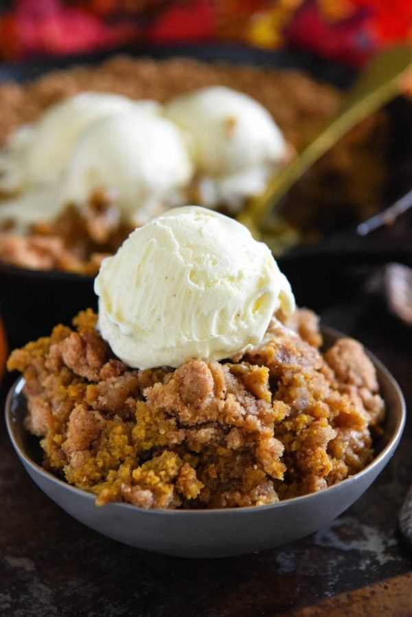 Pumpkin pie crisp with streusel topping in a bowl with ice cream on top.