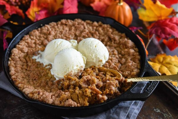 Pumpkin Pie Crisp in cast iron skillet with ice cream on top.