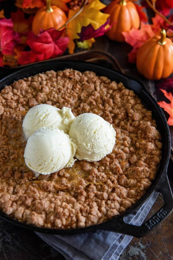 Pumpkin Pie Crisp fresh out of the oven topped with three scoops of vanilla ice cream.