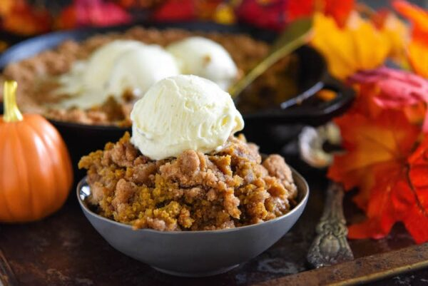 Pumpkin Pie Crisp served warm in a bowl topped with a big scoop of vanilla ice cream.