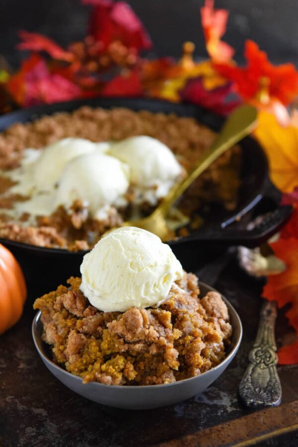 Pumpkin Pie Crisp in cast iron skillet and scooped into a bowl and topped with vanilla ice cream