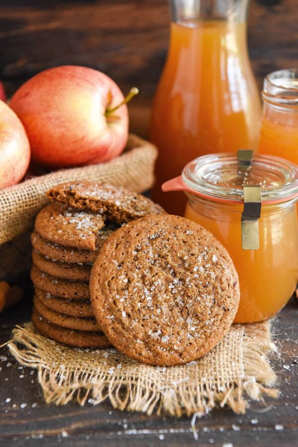 Apple Cider Cookies stacked in a tall stack with real apple cider and apples in baskets