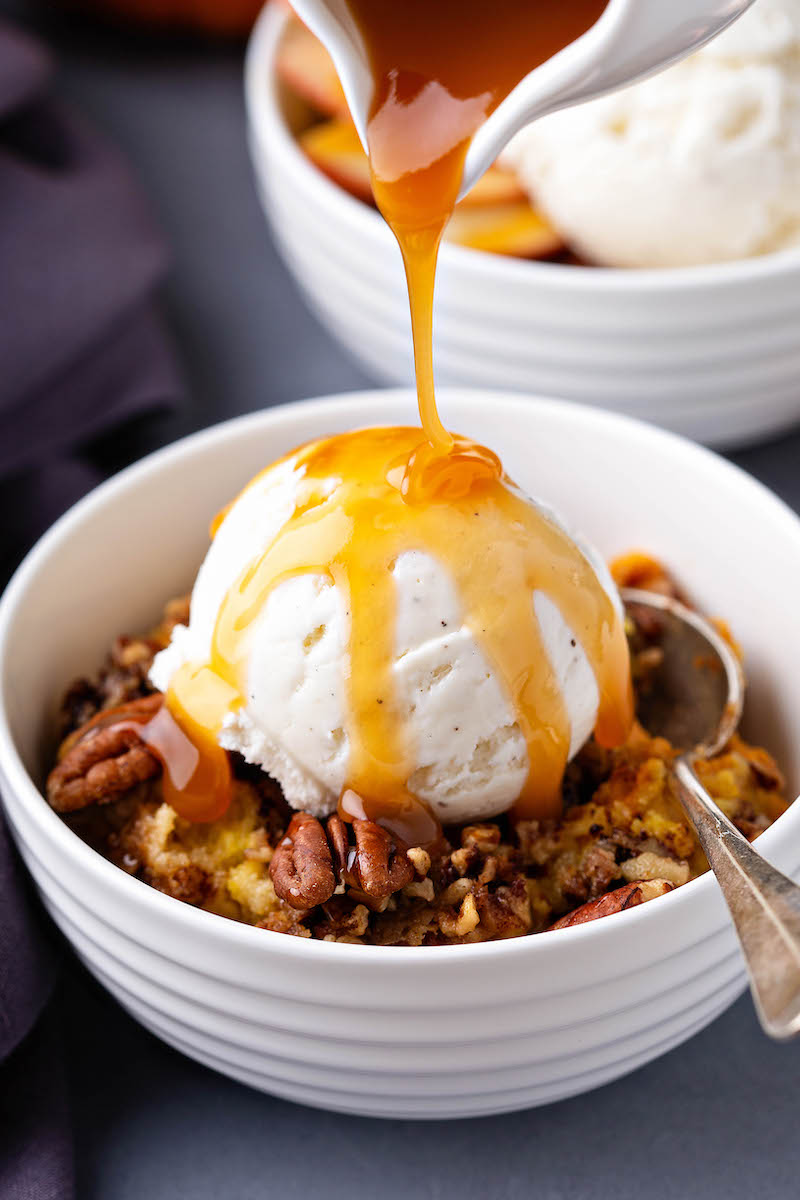 Pumpkin Pecan Cobbler served in a bowl with a spoon, vanilla ice cream on top and a drizzle of caramel sauce on top.