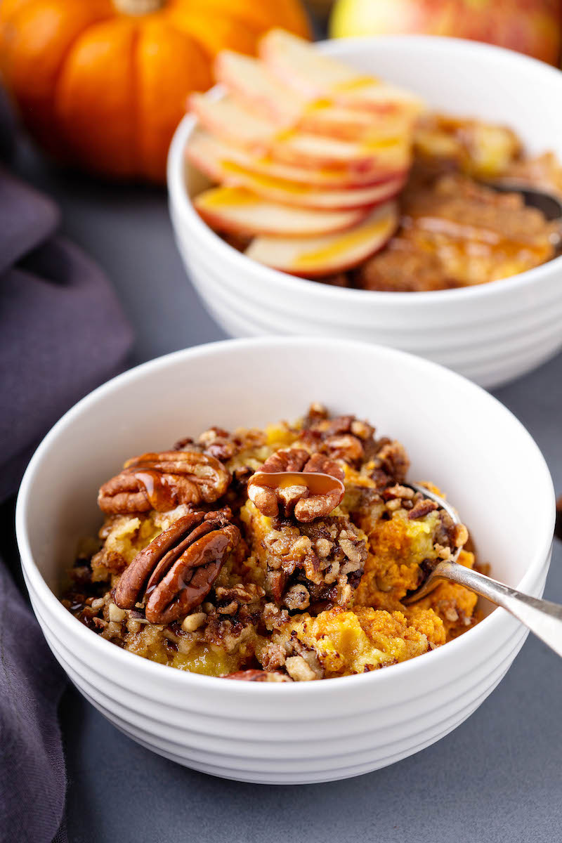 Pumpkin Pecan Cobbler in a big bowl after baking topped with extra pecans and a light caramel drizzle.