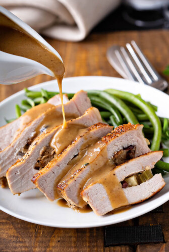 Stuffed pork chops are sliced and being drizzled with brown gravy.