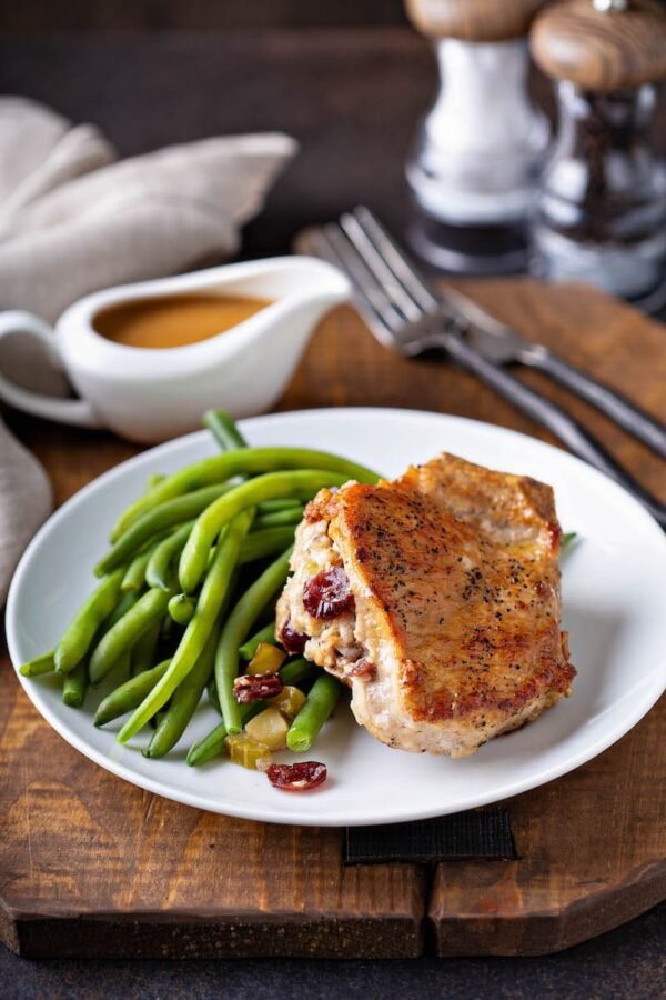 Cranberry Apple Stuffed Pork Chop on a plate with green beans and a gravy boat filled with gravy.